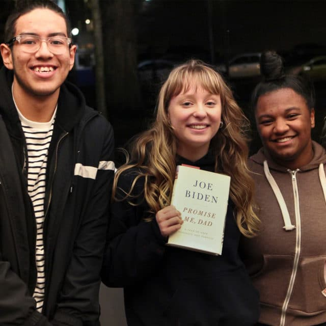 Group of students holding book by former Vice President