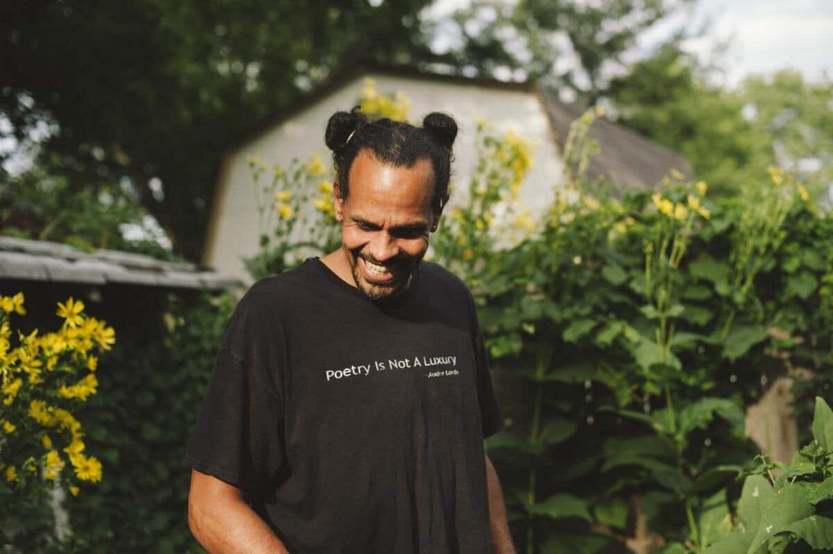 Photograph of the poet Ross Gay smiling while looking down and away from the camera amongst flowers in a backyard.