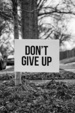 "Black and white photo of a sign saying ""Don't give up hope."""